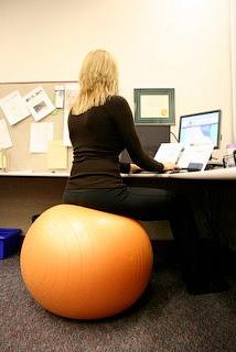 Рата сидя за компьютером на большом гимнастическом мяче